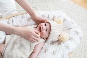 クーファンで寝て母親にあやされる笑顔の赤ちゃんの写真素材 [FYI02675466]