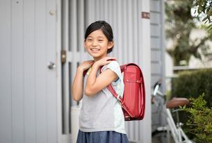 玄関前で微笑むランドセルを背負った女の子の写真素材 [FYI02675489]