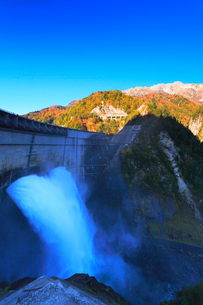秋の立山・黒部ダム観光放水と快晴の空に紅葉の写真素材 [FYI02675649]
