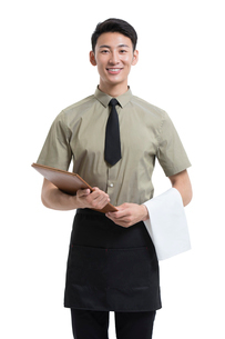 Young Chinese waiter holding a menuの写真素材 [FYI02675922]
