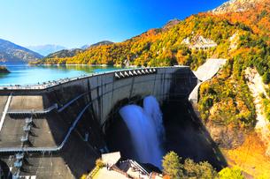 秋の立山・黒部ダム観光放水と快晴の空に紅葉の写真素材 [FYI02675938]