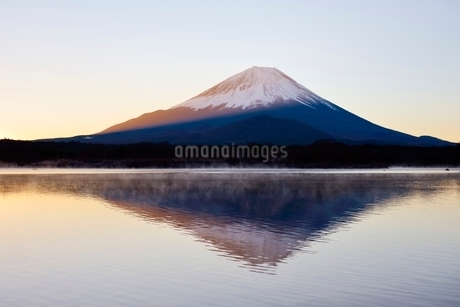気嵐が立つ精進湖より望む夜明けの富士山と逆さ富士の写真素材 [FYI02676407]