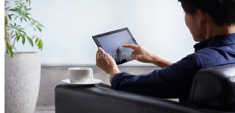 ソファーでタブレット端末を操作する男性の写真素材 [FYI02676593]