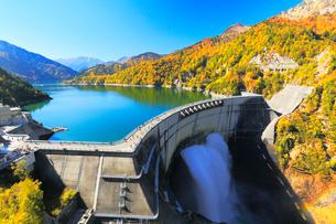 秋の立山・黒部ダム観光放水と快晴の空に紅葉の写真素材 [FYI02676603]