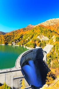 秋の立山・黒部ダム観光放水と快晴の空に紅葉の写真素材 [FYI02676658]
