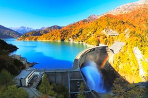 秋の立山・黒部ダム観光放水に虹と快晴の空に紅葉の写真素材 [FYI02677043]