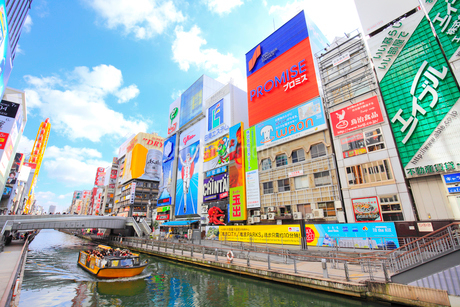 大阪道頓堀の商業ビルと川を遊覧するとんぼりリバークルーズの写真素材 [FYI02677328]