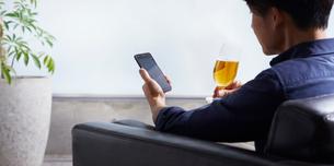 ビールを飲みながらスマホを操作する男性の写真素材 [FYI02677342]