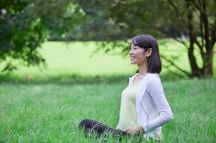 緑の中でヨガをする女性の写真素材 [FYI02678277]