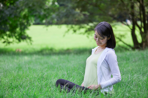 緑の中でヨガをする女性の写真素材 [FYI02678310]