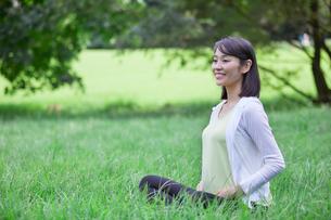 緑の中でヨガをする女性の写真素材 [FYI02678439]