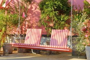 フラワーショップの前にあるピンクのブランコの写真素材 [FYI02678701]