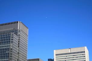 新丸ビル上空を飛ぶ飛行機の写真素材 [FYI02679387]