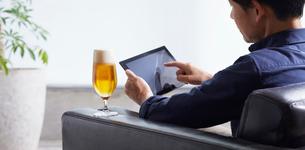 ビールを飲みながらタブレット端末を操作する男性の写真素材 [FYI02679537]