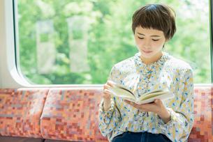 電車で読書をする女性の写真素材 [FYI02680759]