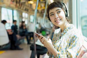 電車で音楽を聴く女性の写真素材 [FYI02680768]