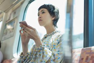 電車で音楽を聴く女性の写真素材 [FYI02680886]
