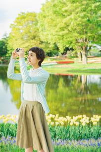 花畑で写真を撮る若い女性の写真素材 [FYI02680902]