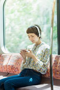 電車で音楽を聴く女性の写真素材 [FYI02681001]