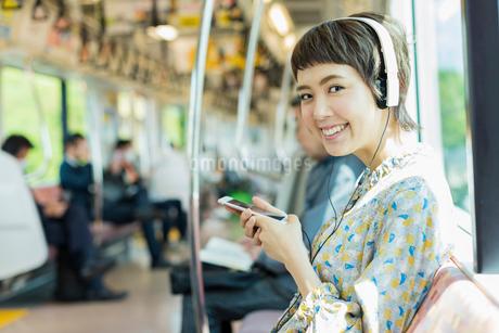 電車で音楽を聴く女性の写真素材 [FYI02681156]