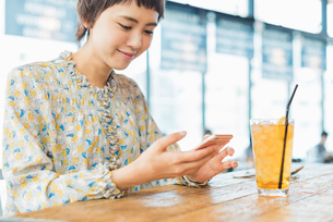 カフェでスマホを使う女性の写真素材 [FYI02681225]