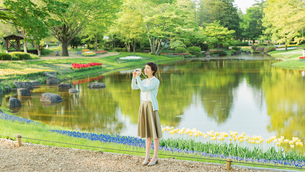 花畑で写真を撮る若い女性の写真素材 [FYI02681230]