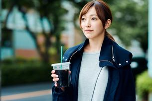 街中でアイスコーヒーを飲む若い女性の写真素材 [FYI02681281]