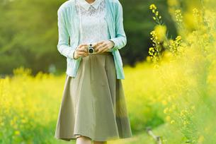 菜の花畑で写真を撮る若い女性の写真素材 [FYI02681308]