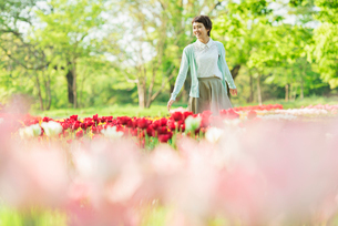 花畑で写真を撮る若い女性の写真素材 [FYI02681310]