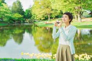 花畑で写真を撮る若い女性の写真素材 [FYI02681313]