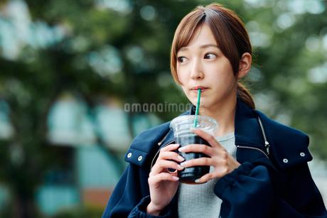 街中でアイスコーヒーを飲む若い女性の写真素材 [FYI02681341]