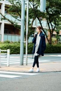街中でアイスコーヒーを飲む若い女性の写真素材 [FYI02681470]