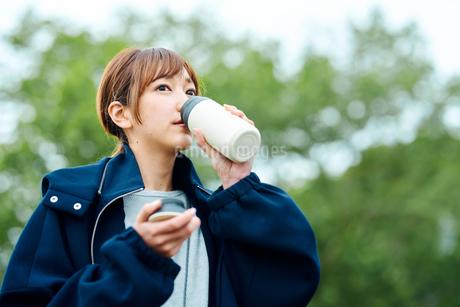 温かい飲み物を飲む若い女性の写真素材 [FYI02681637]
