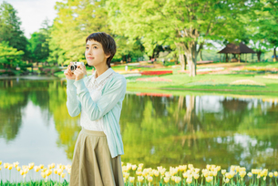 花畑で写真を撮る若い女性の写真素材 [FYI02681769]