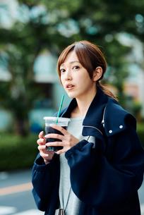 街中でアイスコーヒーを飲む若い女性の写真素材 [FYI02681866]