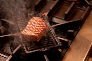 グリルで焼かれている赤味が残る肉の写真素材 [FYI02681903]