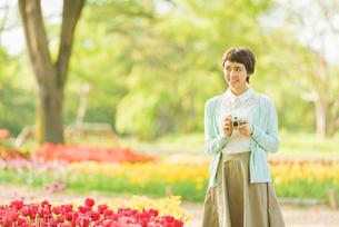 花畑で写真を撮る若い女性の写真素材 [FYI02682121]