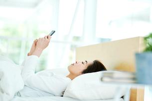 ベッドの上でスマートフォンをチェックする女性の写真素材 [FYI02682147]