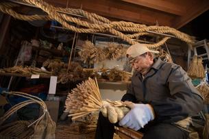冬の農閑期にしめ縄作りする80代男性の写真素材 [FYI02682297]