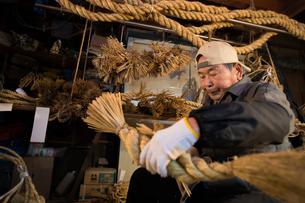 冬の農閑期にしめ縄作りする80代男性の写真素材 [FYI02682469]