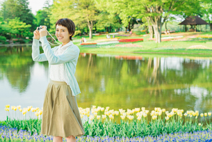 花畑で写真を撮る若い女性の写真素材 [FYI02682529]