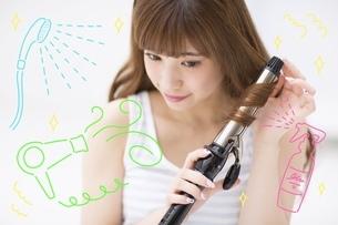 ヘアアイロンで髪を巻く女性のイラスト素材 [FYI02682588]