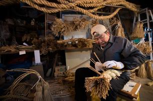 冬の農閑期にしめ縄作りする80代男性の写真素材 [FYI02682657]