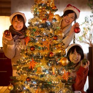 クリスマスツリーの周りで微笑む若者たちの写真素材 [FYI02682798]