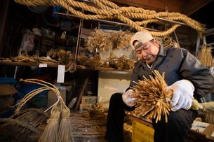 冬の農閑期にしめ縄作りする80代男性の写真素材 [FYI02682820]