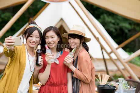 グランピングテントの前で自撮りをする若者たちの写真素材 [FYI02682877]