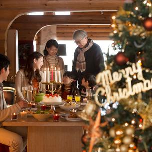 クリスマスパーティーをする3世代家族とクリスマスツリーの写真素材 [FYI02682882]