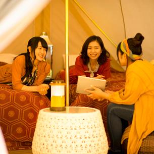 グランピングテントの中で談笑をする若者たちの写真素材 [FYI02682948]