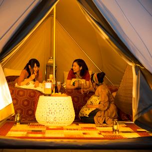 グランピングテントの中で談笑をする若者たちの写真素材 [FYI02682959]