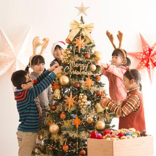 クリスマスツリーに飾り付けをする子供達の写真素材 [FYI02682974]
